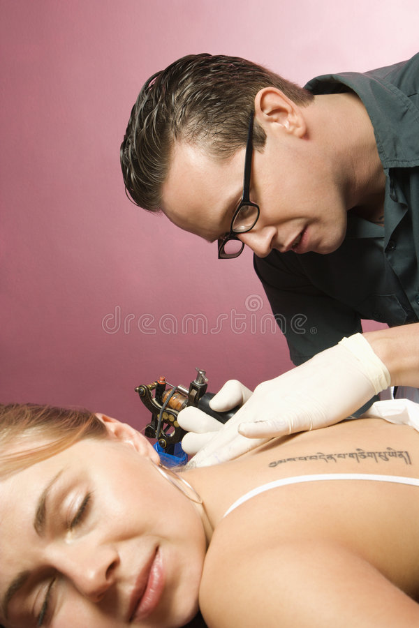Man tattooing woman. stock images
