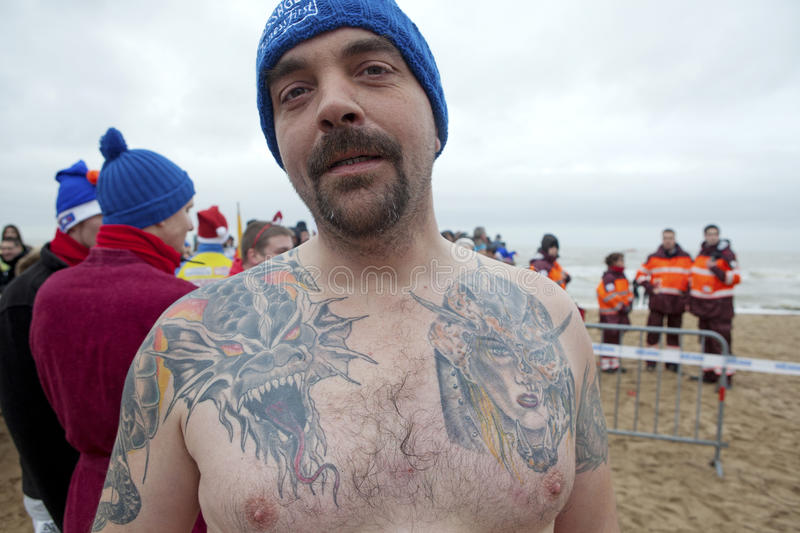 Man with tattoos, Belgium. Man showing his tattoos on his chest and arms on the beach in Belgium stock image