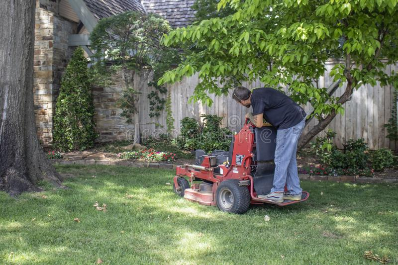 Man with tattoos on standing commercial lawnmower cutting a close circle around tree and flowerbeds in upscale. Tulsa USA 6 22 2018 Man with tattoos on standing royalty free stock image