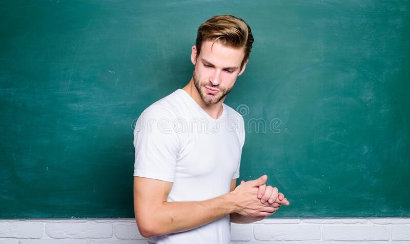 Man teacher in front of chalkboard. Teaching could be more fun. Advantages for male elementary teacher are abundant. Teacher speaker lecturer. Source of energy stock photography