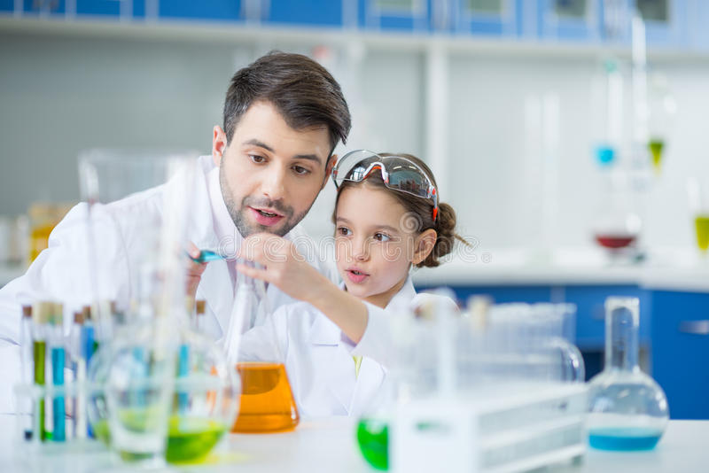 Man teacher and girl student scientists making experiment. In chemical lab stock images
