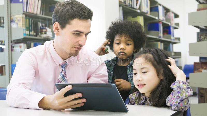 Man teacher and kid students learning and looking on tablet devi royalty free stock photography