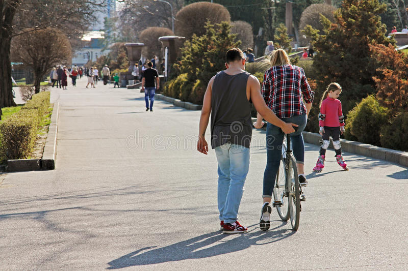 Man teaches a woman to ride a bicycle in park in Volgograd stock images