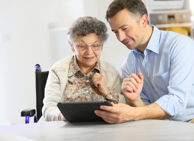 Man teaching elderly lady how to use tablet stock photo