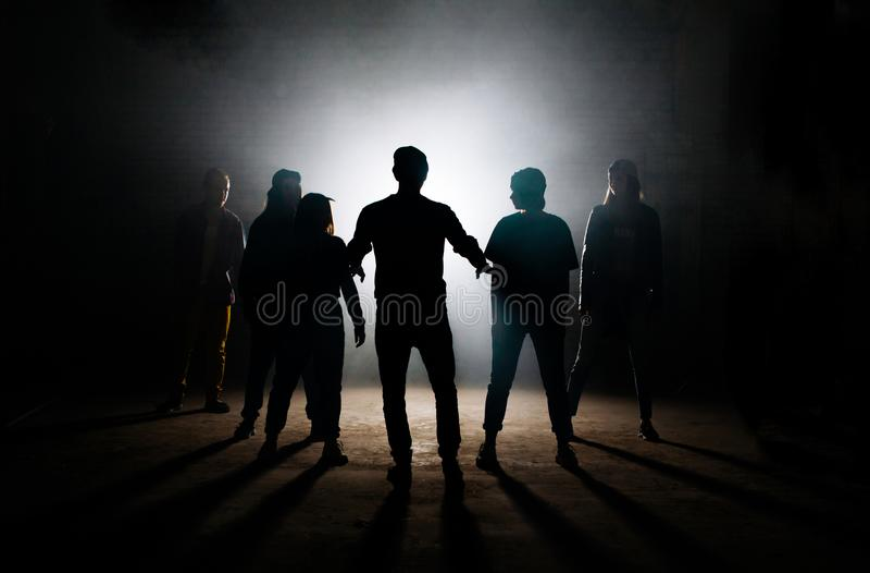 Man teaching his friends hip hop on the dark studio stock image