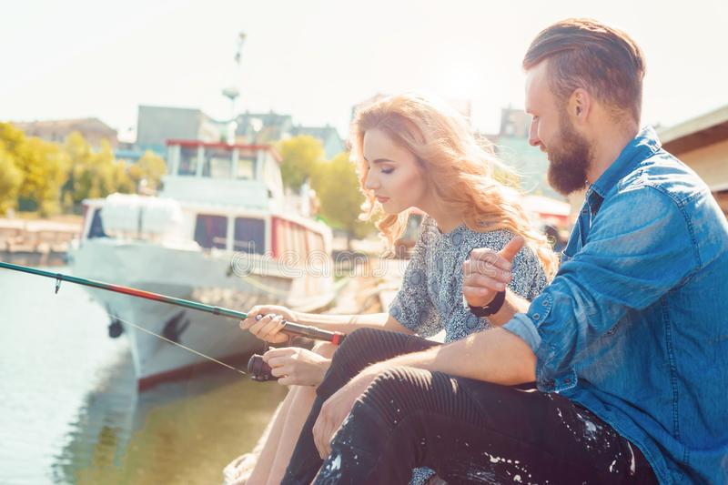 Man teaching his girlfriend to fishing. Date, love and hobby concept. Autumn background. stock photo
