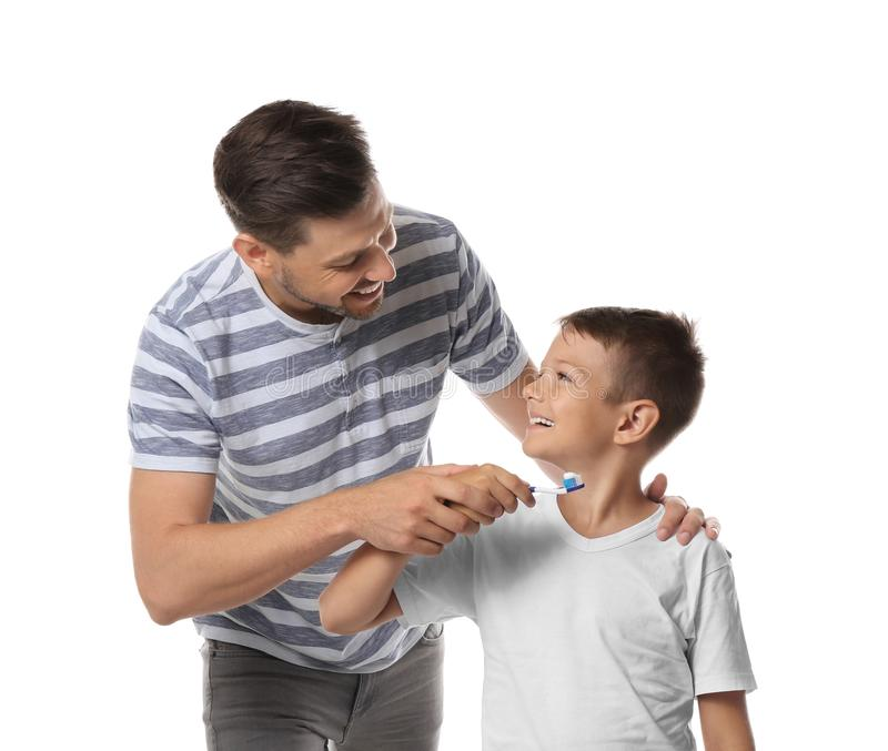 Man teaching his little son how to brush teeth on white background royalty free stock photography