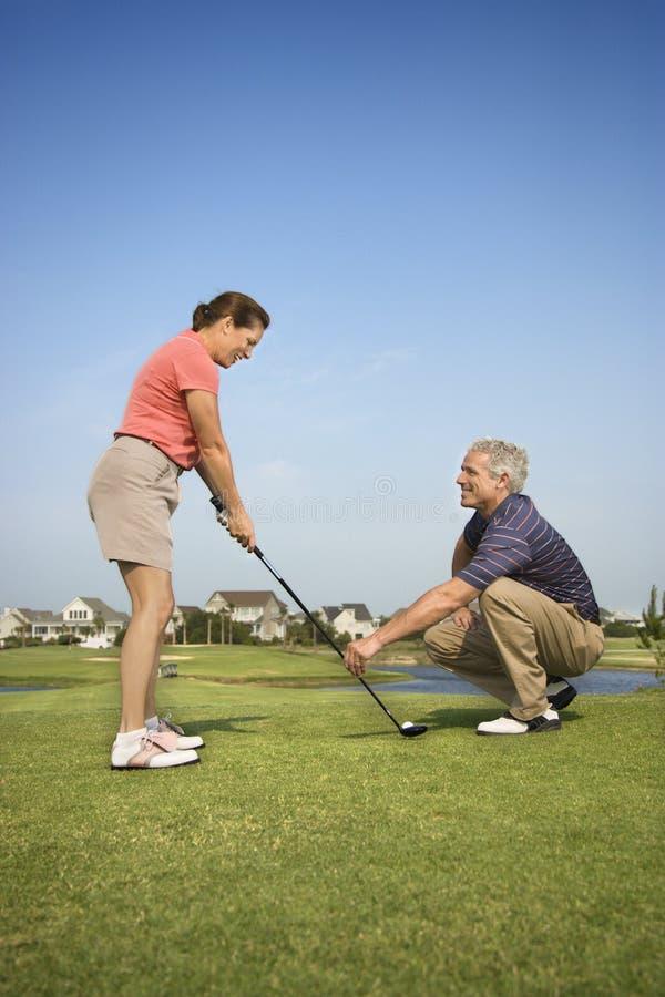 Man teaching woman golf royalty free stock photography