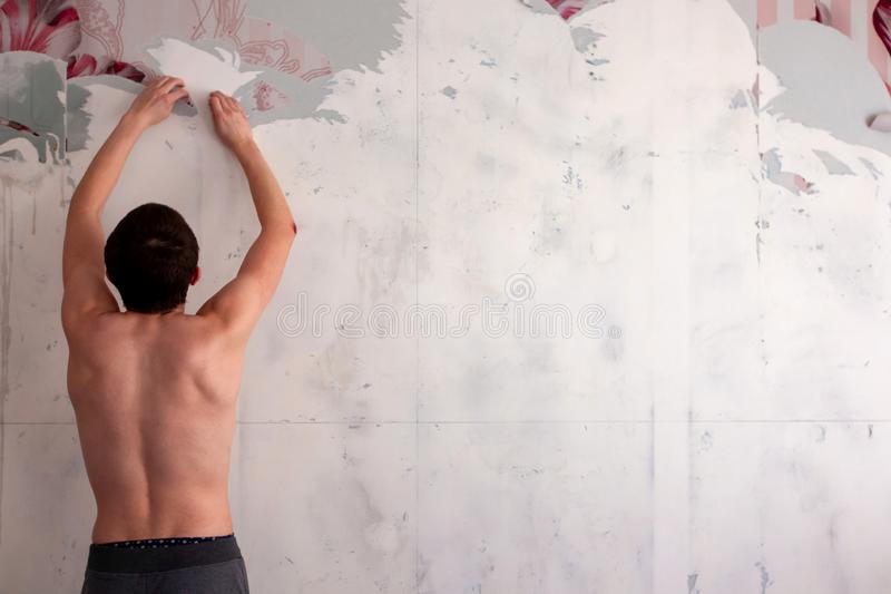 A man tears off the Wallpaper, removing Wallpaper from the wall with a spatula, the process of updating the wall repair of the royalty free stock image