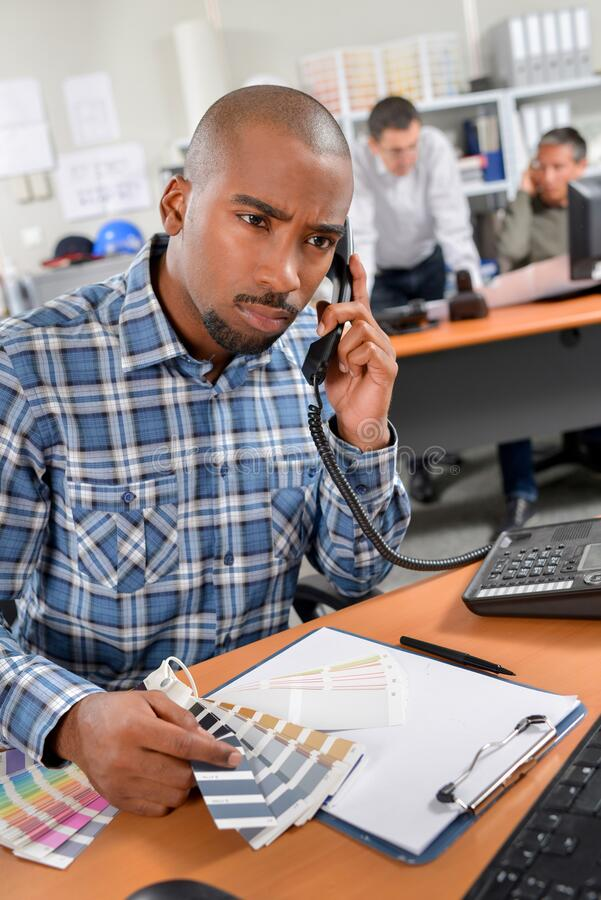 Man on telephone holding colour charts looking confused. African royalty free stock images
