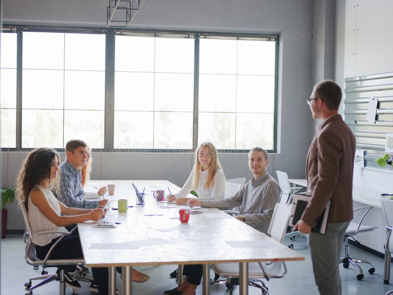 A man tells his business plan to a group of office workers stock image