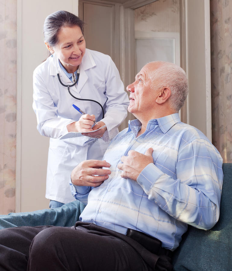 Man tells the mature doctor the symptoms stock photos