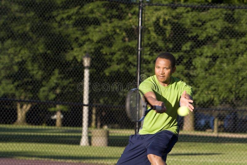 Man on Tennis Court Playing Tennis - Horizontal royalty free stock photo