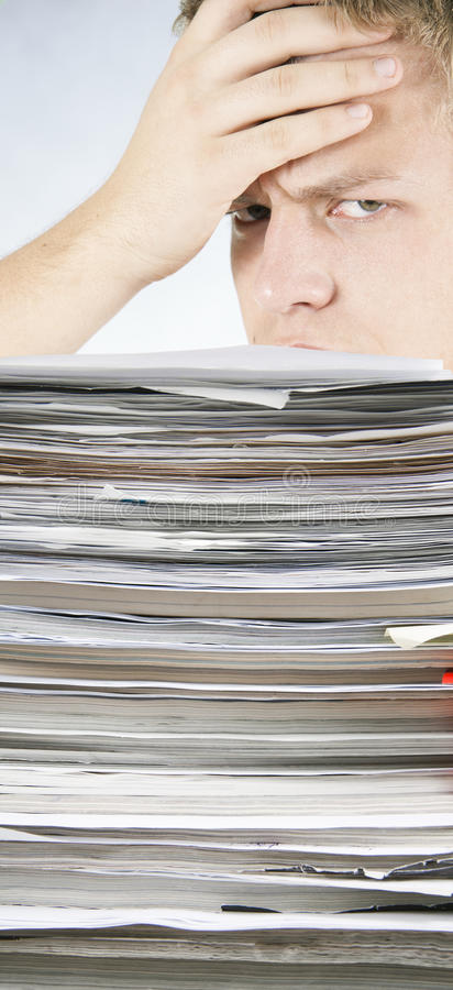Free Man Tensely Looks At A Bale Of Papers Royalty Free Stock Photography - 17950957