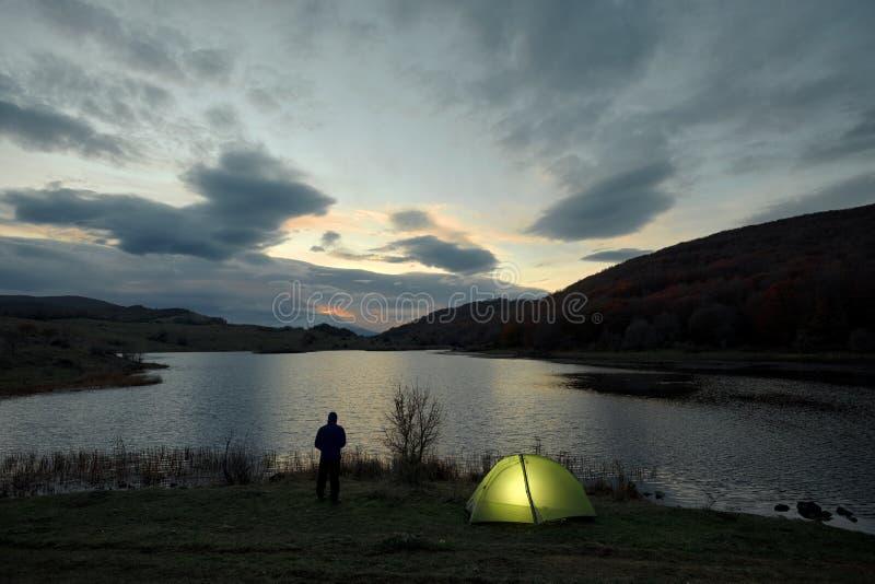 Man And Tent Against Sunrise On Lake Nebrodi Park, Sicily stock photo