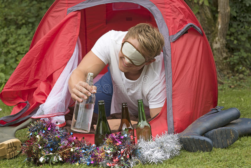 Man in tent reaching for water. CAMPING PARTY TIME - A camper reaches outside his tent for a water bottle royalty free stock image