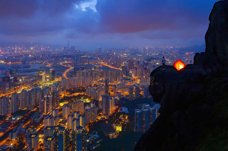A man with tent standing on Suicide cliff in Hong Kong Downtown, China. Financial district and business centers in technology stock images