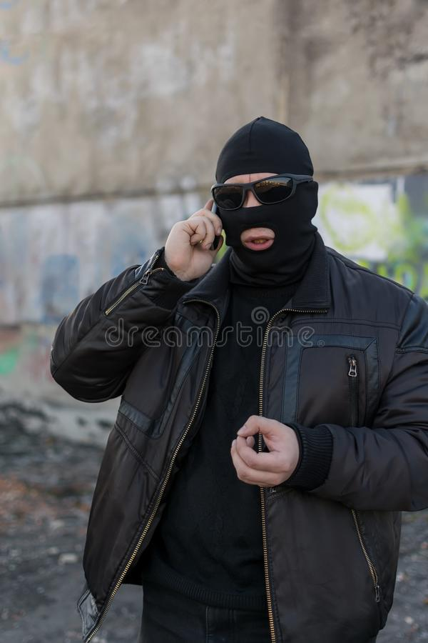A bandit in a black leather jacket and a mask talking on the phone on the street near an abandoned building. A man, a terrorist, a bandit in a black leather royalty free stock images