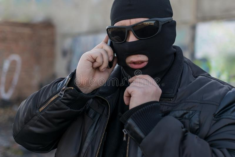 A terrorist, a bandit in a black leather jacket and a mask talking on the phone. A man, a terrorist, a bandit in a black leather jacket and a mask talking on the royalty free stock image