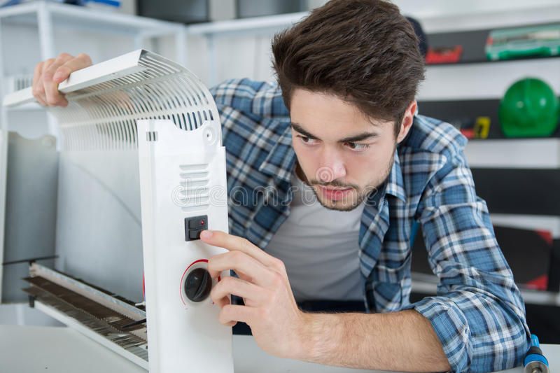 Man testing heating on wall royalty free stock photo
