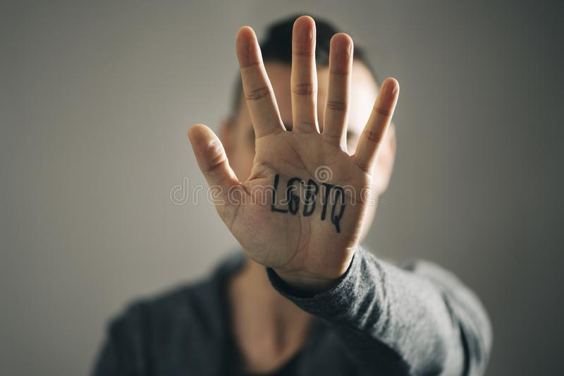 Man with the text LGBTQ in his hand. Closeup of a young caucasian man with the palm of his hand in front of his face with text LGBTQ, for lesbian, gay, bisexual stock photography