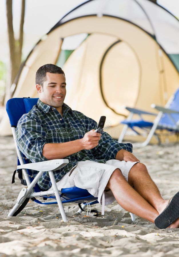Man text messaging on cell phone at campsite. Man text messaging on his cell phone at campsite stock image