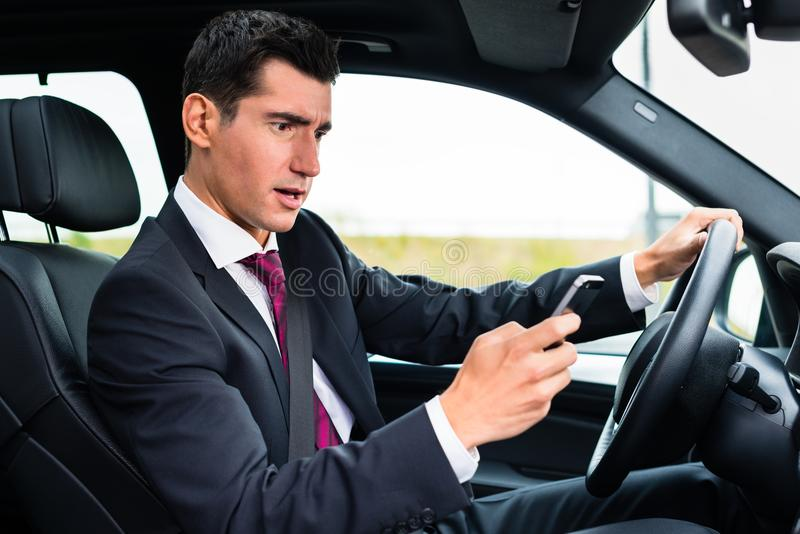 Man texting while driving by car. Man texting on his phone while driving by car royalty free stock images