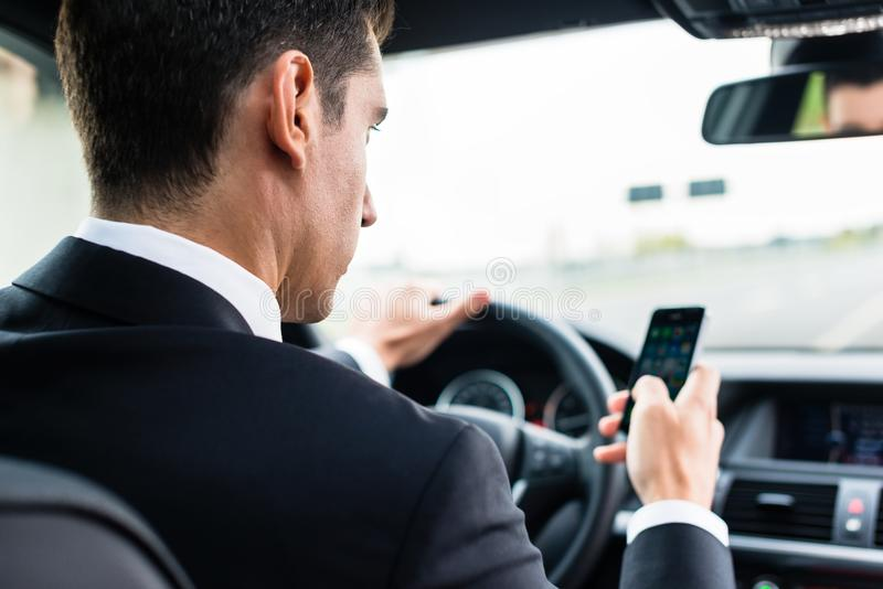 Man texting while driving by car. Man texting on his phone while driving by car royalty free stock photo