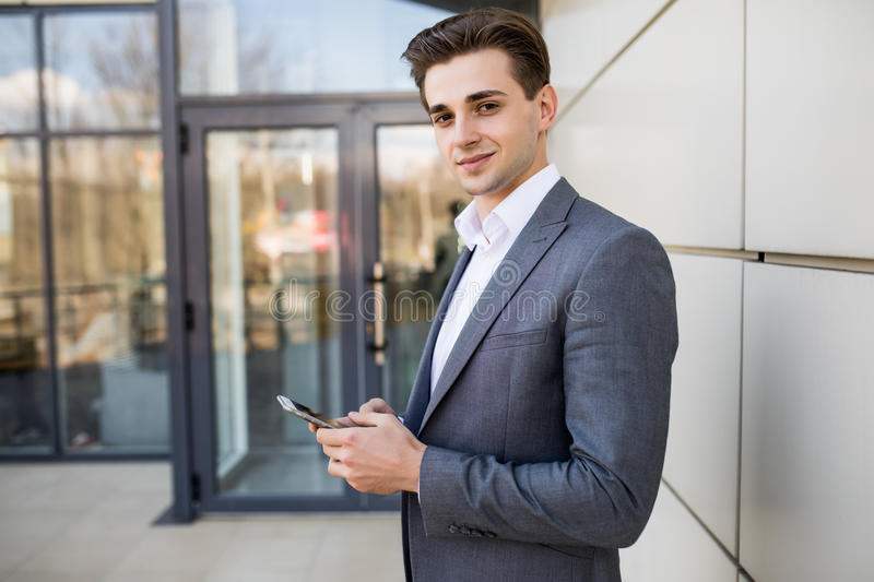 Man texting on phone. Casual urban professional entrepreneur using smartphone smiling happy outside office building. royalty free stock photography
