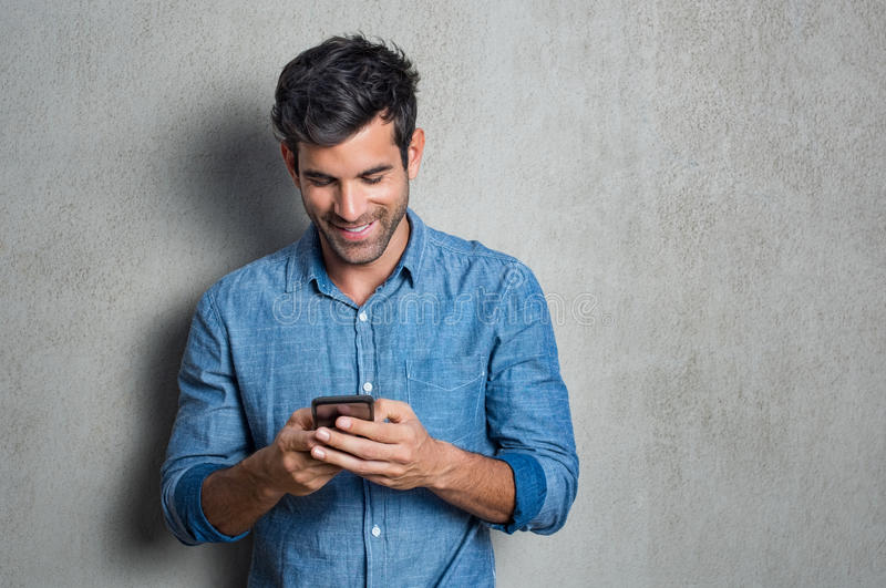 Man texting on phone. Young man texting message on smart phone isolated on grey background. Smiling latin man holding smartphone and looking at it. Happy