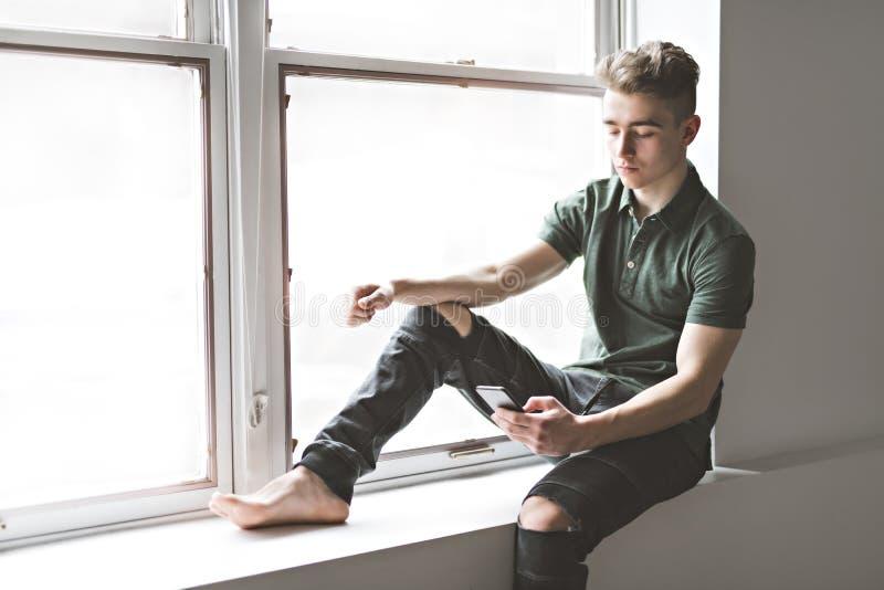 Man texting sit ont the window border. A Man texting sit ont the window border royalty free stock photos