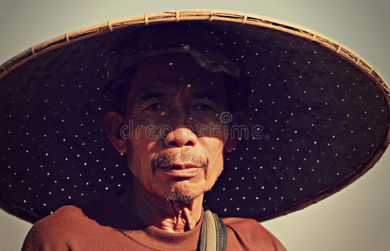 A man in Thailand wears a large bamboo hat. A man in Thailand wears a goatee and a dour expression stock image