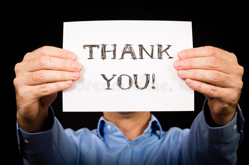 Man with Thank You sign. Studio shot of man holding white sign with the words Thank You stock photography