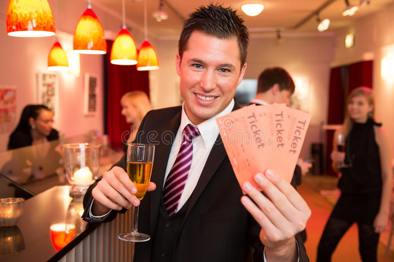 Man in a theatre or cinema presenting tickets stock images