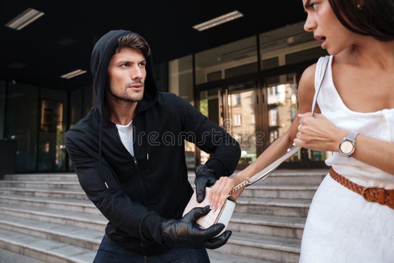 Man thief in black hoodie stealing woman bag stock image