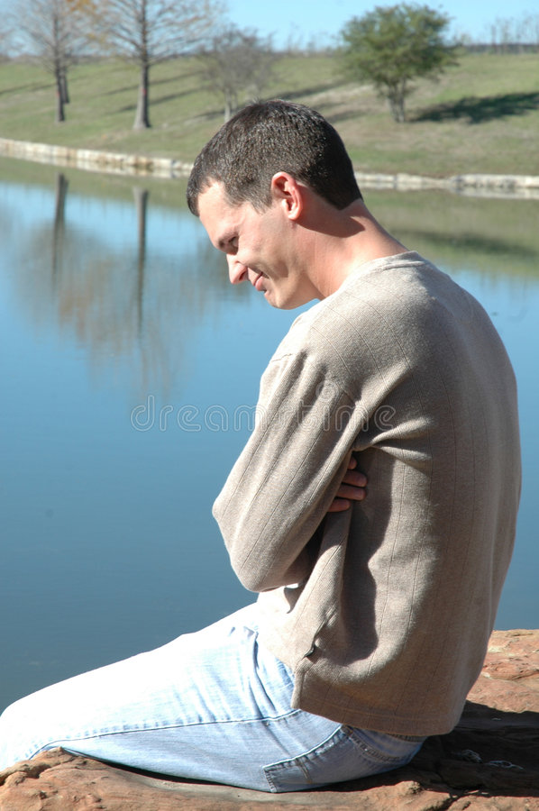 Man thinking. Profile of A man in casual clothing sits alone on a rock by a pond with his arms crossed. Man sitting in a park or nature park. Man being royalty free stock photo