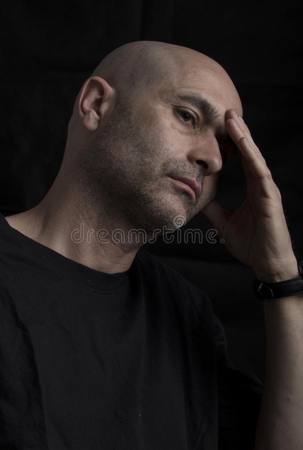 Worried man thinking on black background stock photos