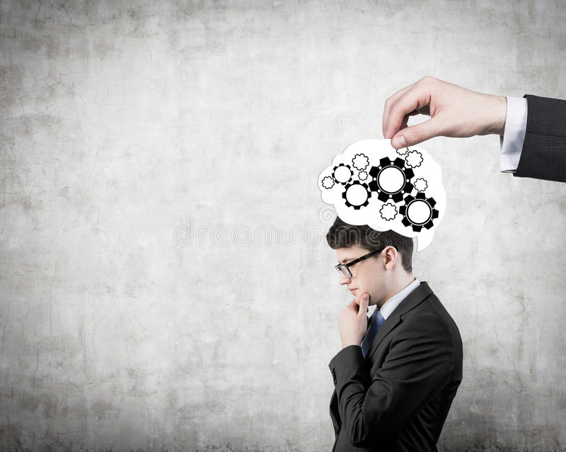 Man thinking. Businessman thinking and cogs and gears in hand royalty free stock image