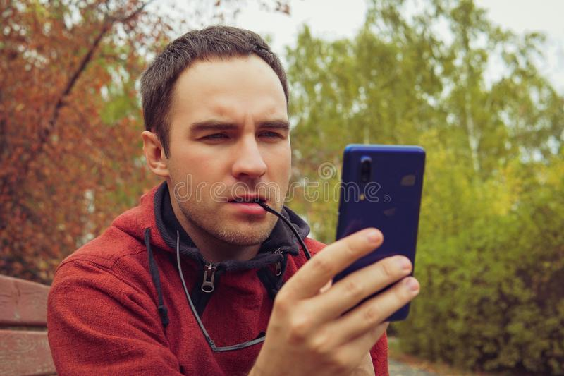 Man thinking curiously, holding a smartphone, sitting outdoor in garden. A young guy looks indignantly at the screen of stock photos
