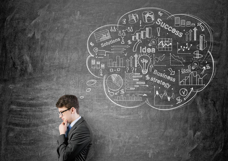 Man thinking about financial growth. Young pensive businessman thinking about success and financial growth on chalkboard background stock images