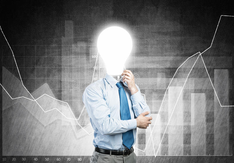 Man thinking over his idea. Pensive businessman with lamp head on concrete background stock photo