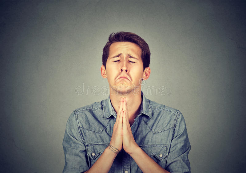 Man thinking and praying with eyes closed stock photo
