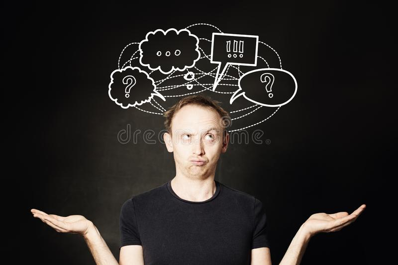 Man thinking with question mark and hand drawing sketch bubble on blackboard background. Choice, problem and solution concept royalty free stock images