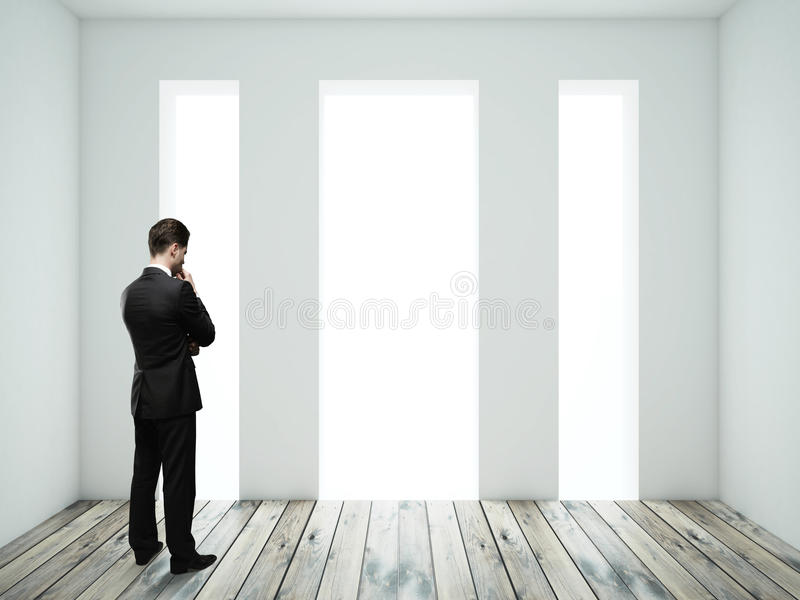 Man thinking in room. Businessman thinking in room with wooden floor royalty free stock photography