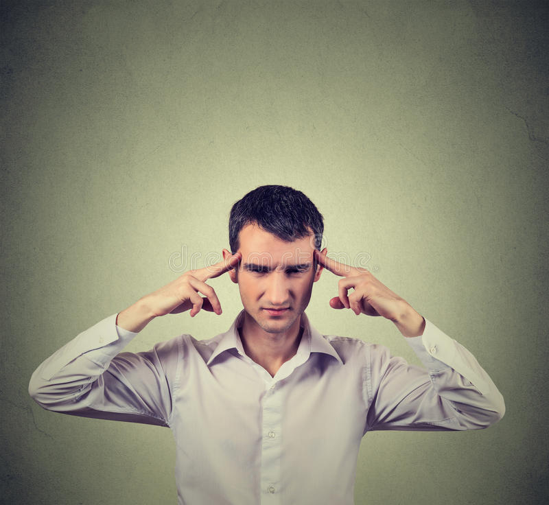 Man thinking very intensely concentrating. Isolated on gray wall background stock photos