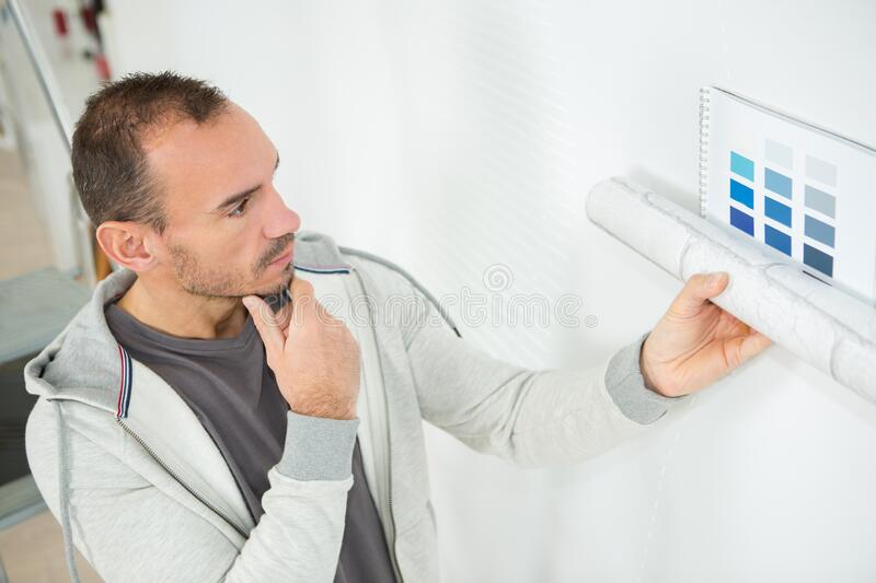Man thinking wall color. Man thinking of wall color stock photo