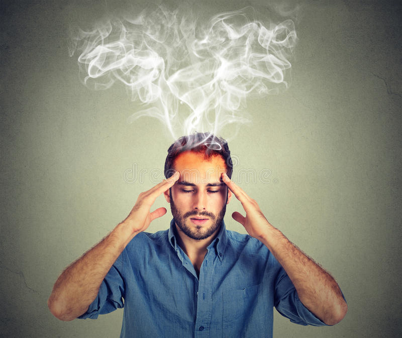 Man thinks very intensely having headache. Isolated on gray wall background stock images