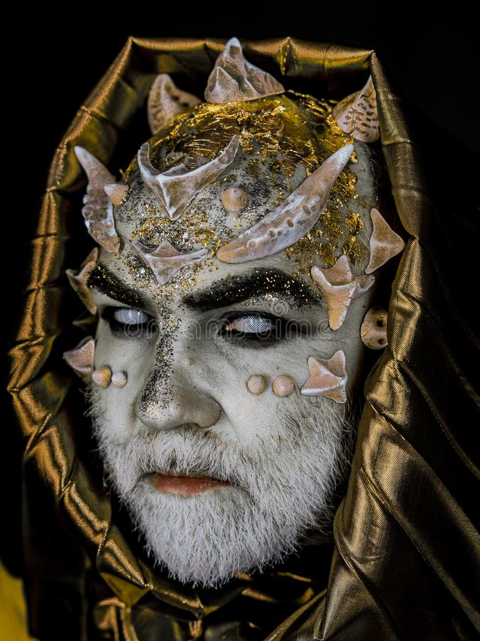 Man with thorns or warts, face covered with glitters. Senior man with white beard dressed like monster. Alien, demon stock photos