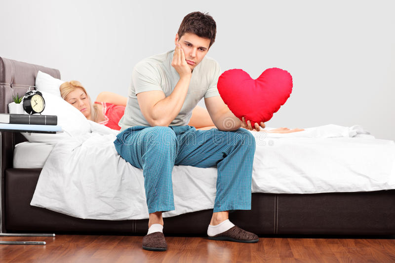 Man in thoughts holding a heart shaped pillow. Young men in thoughts holding a heart shaped pillow while his girlfriend fall asleep royalty free stock image