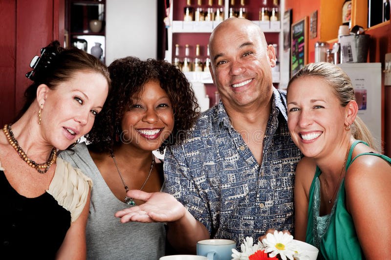 Man with three pretty women in coffee house. Man with shaved head and three pretty women in coffee house royalty free stock images